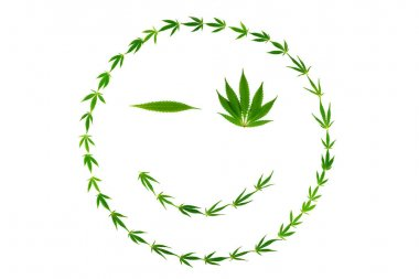 Winking face as smiley made of hemp leaves