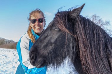 Portrait dutch woman with frisian horse in winter