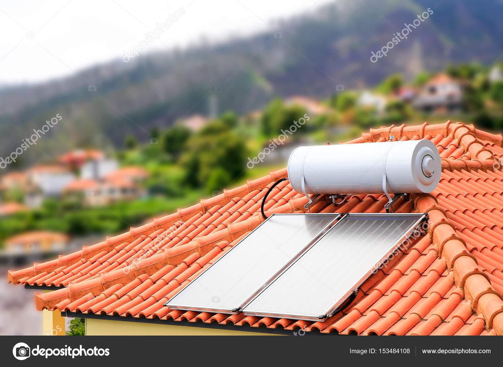 Wasserkocher mit Sonnenkollektoren auf dem Dach des Hauses ...