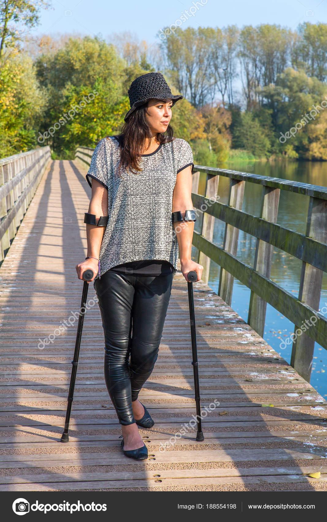 Frau mit Krücken gehen auf Brücke — Stockfoto © benschonewille #188554198