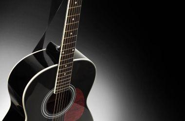 Black acoustic guitar on a black background