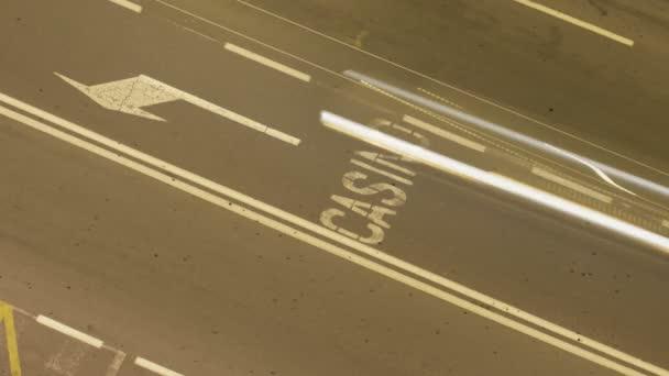 statische mittlere Höhe Overhead-Zeitraffer-Aufnahme in der Nacht einer Straße mit dem Wort Casino und einem Linksabbiegezeichen auf dem Asphalt, mit blinkenden Lichtzeichen des vorbeifahrenden Verkehrs.
