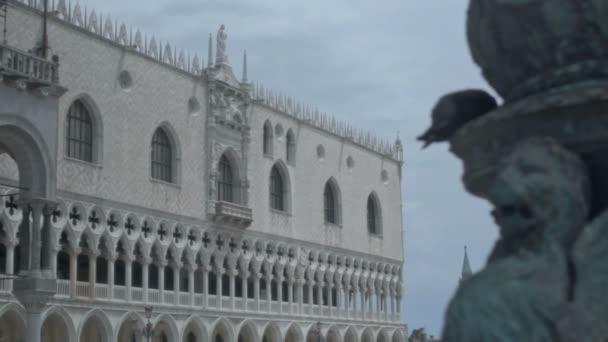 Středně dlouhý nízký úhel malou hloubku pole sledování snímku během slunečného dne na kolonádě s jetelem, který formoval kresby Dóžecí palác v Benátkách, lev Venice a San Giorgio Maggiore zvonice v pozadí