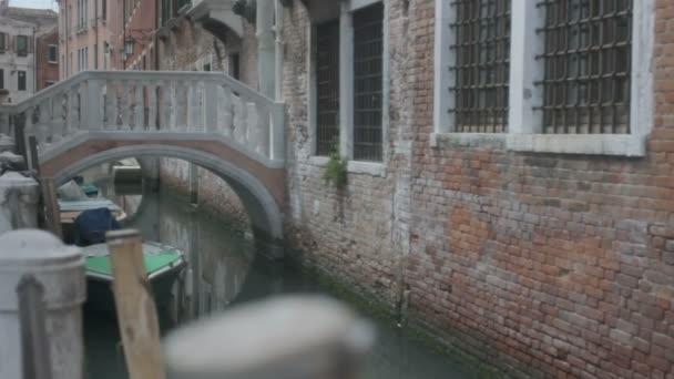 Středně dlouho mělká Hloubka pole sledování snímku mostu malé růžové chůze s bílou barokní zábradlí přes malý kanál v Benátkách, což vede k budování s mříže na oknech