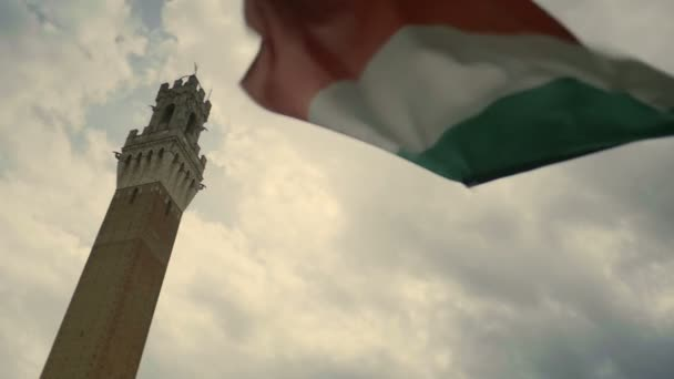 Medium wide low angle handheld shallow depth of field shot of an Italian flag waving in the wind under the Torre del Mangia on the Piazza del Campo in Siena Tuscany Italy during a cloudy day with the sun behind the clouds.