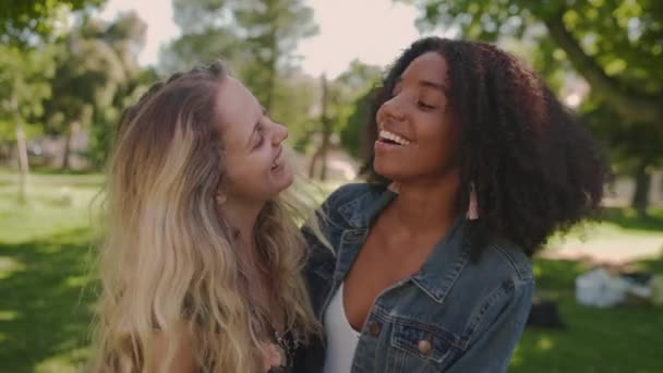 Portrait of two multiracial young woman friends embrace and enjoying friendship in the park - smiling happy friends in the park on a sunny day laughing