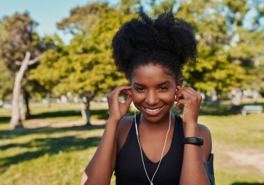 Close-up of a smiling african american young woman before workout listening to music to pump herself up