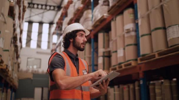 Lagerarbeiter überprüft Inventar im Lagerraum einer Fertigungsfirma auf Touchscreen-Tablet