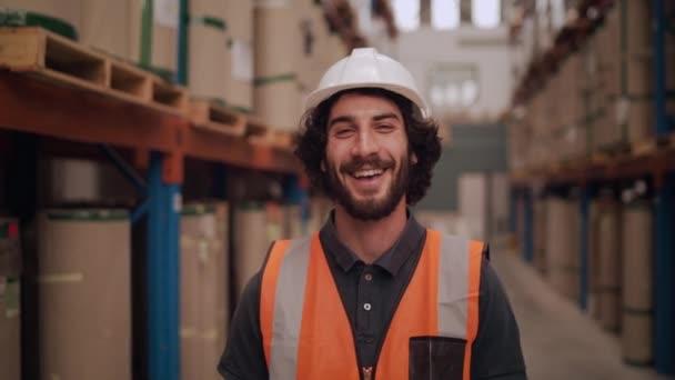 Portrét bělošského skladníka stojícího ve velkém skladovém distribučním centru a usmívajícího se a hledícího do kamery