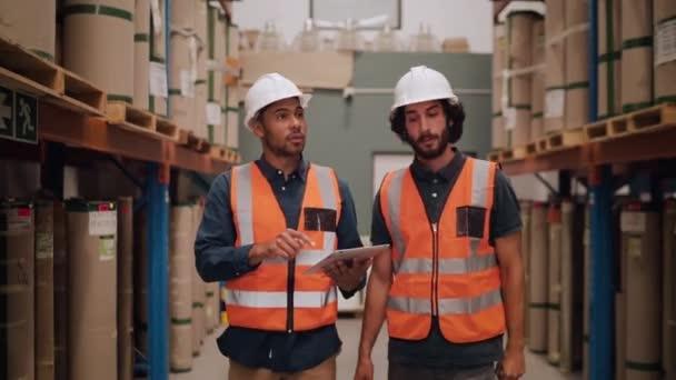 Két keménykalapot és fényvisszaverő kabátot viselő raktármunkás digitális táblagépet használva tartja karban a raktárban a gyártott áruk részleteit.