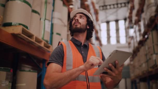 Glückliches Porträt eines männlichen Unternehmers mit Brille und weißem Bollenhut, der in seinem Lager steht und in die Kamera blickt