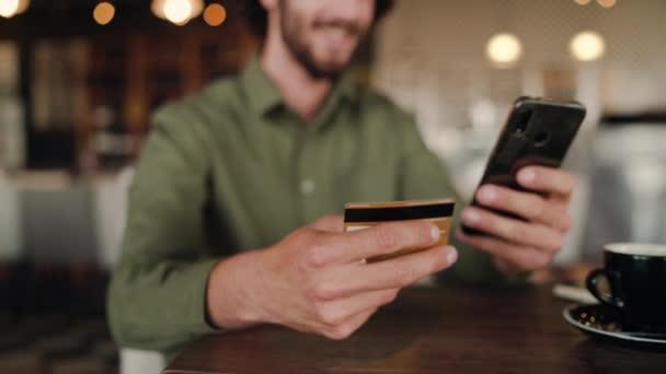 konzentrieren sich auf einen Mann, der online einkauft und mit Bankkarte kauft, während er sich im Café entspannt - Online-Einkäufe