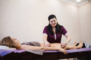 Doctor specialist massage therapist does anti-cellulite massage of legs and buttocks to a beautiful young girl on a massage table, health and beauty, spa and body relaxation