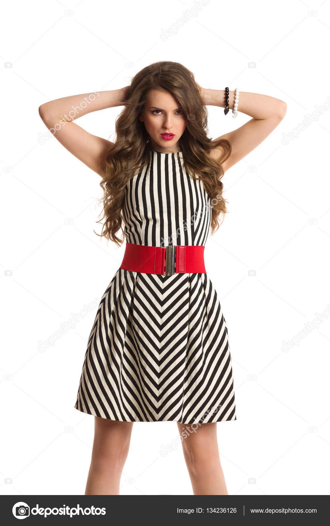 53870e9902fa9d Елегантний молода жінка з довге каштанове волосся, носять чорно-білий смугастий  плаття і Холдинг руки за голову. Три чверті довжина студії вистрілив ...