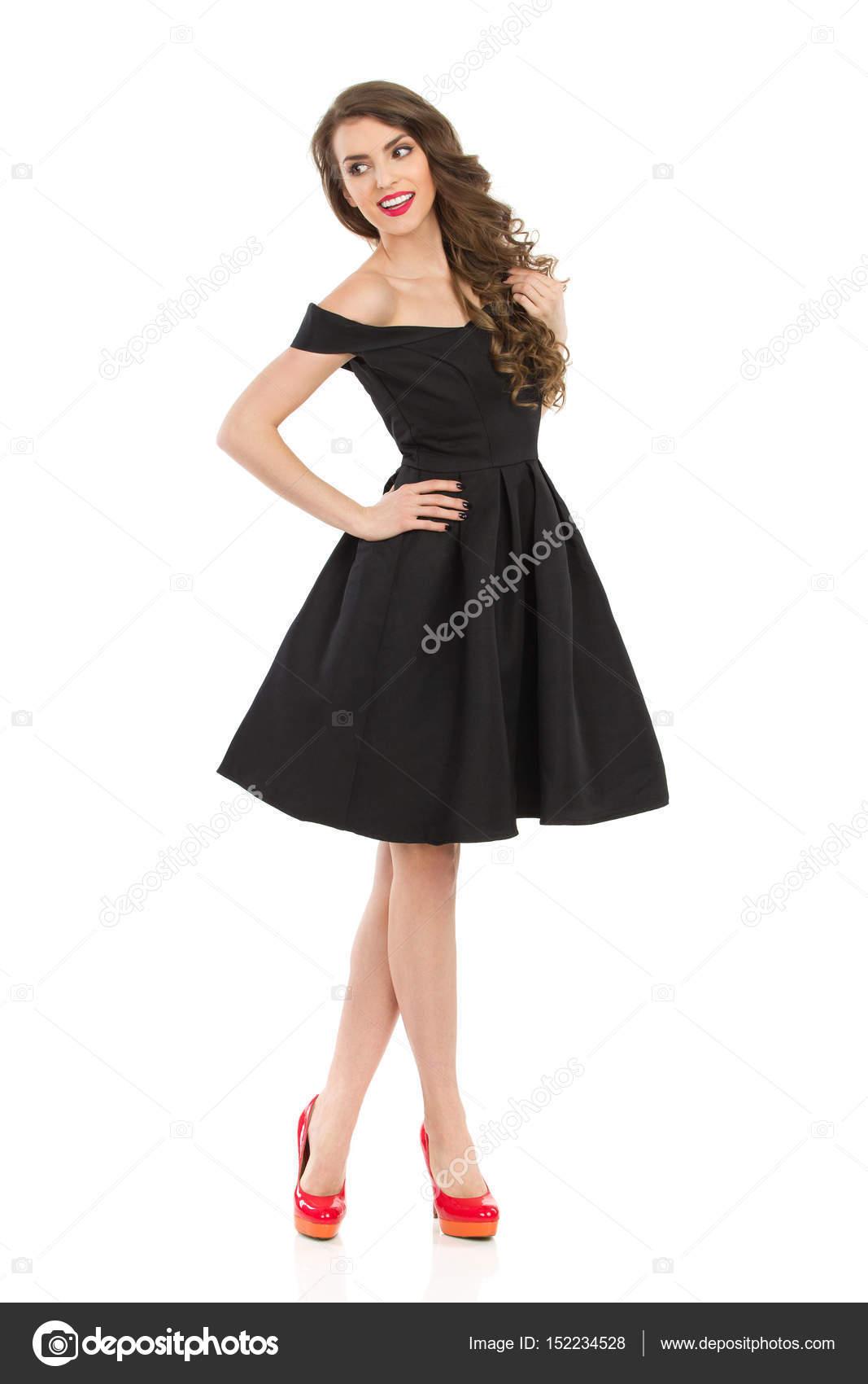 Elegante Dame im schwarzen Cocktailkleid lächelnd sucht Weg ...