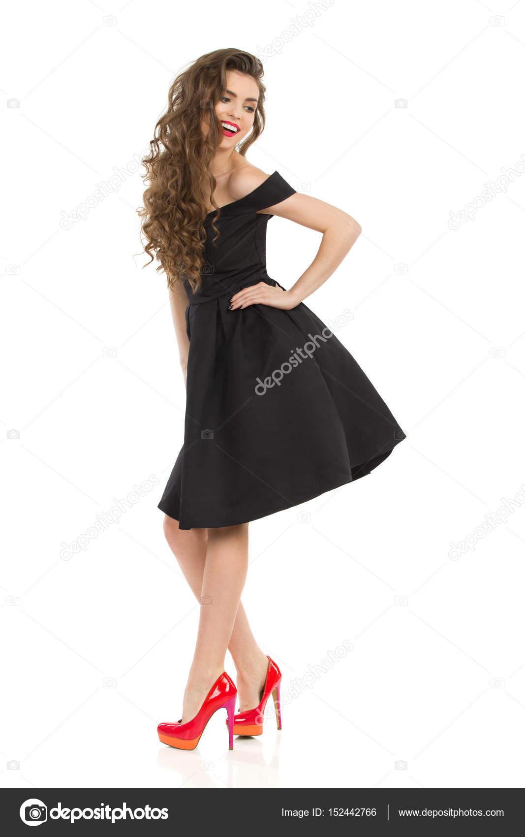 2fe6a392765 Belle jeune femme élégante robe de cocktail noire et talons hauts rouges est  maintenant main sur la hanche et regarder loin par-dessus l épaule.