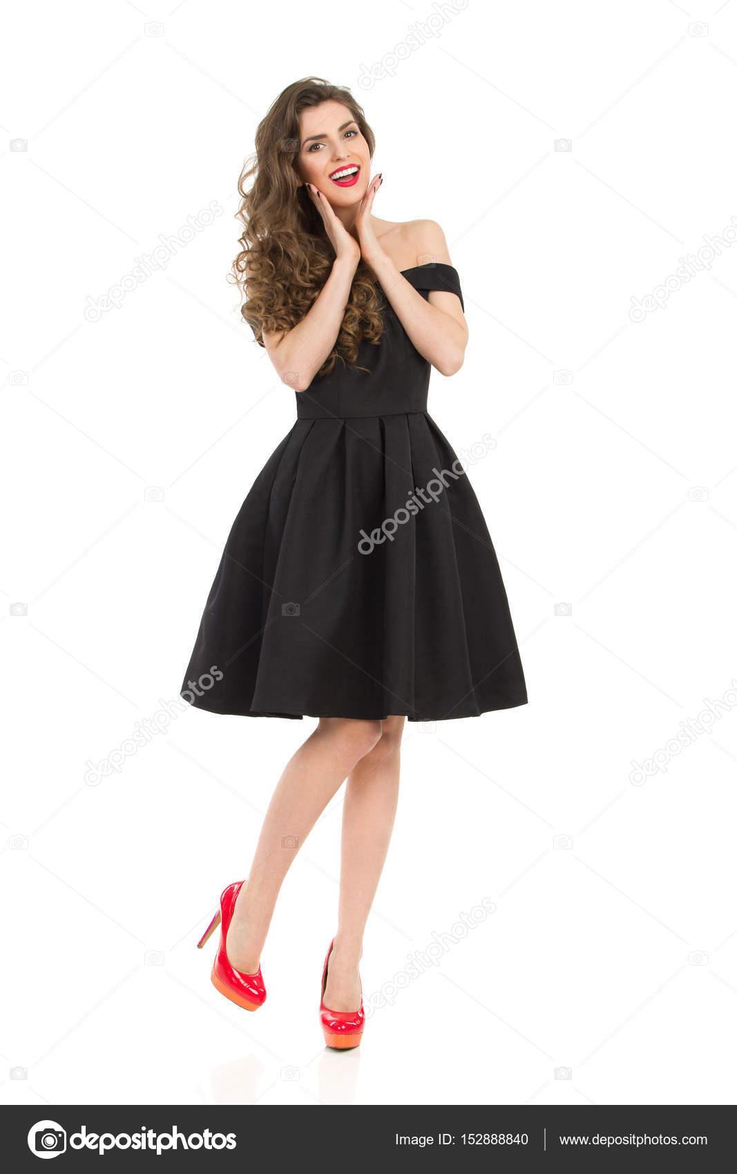 Elegante Dame im schwarzen Kleid und roten High Heels begeistert ...