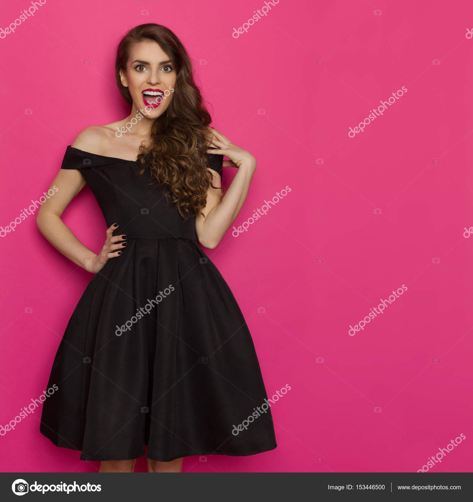 76d214af9bf Amusé de belle jeune femme en robe de cocktail noire élégante est criant et  en regardant la caméra. Trois quarts studio longueur tourné sur fond rose  ...