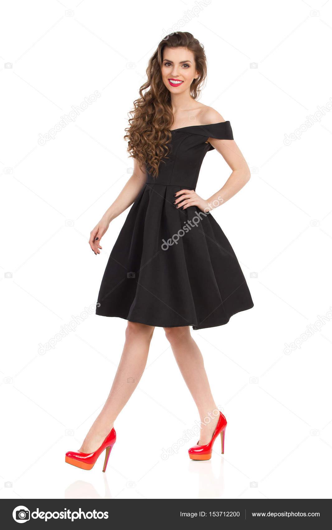4e3f258a32e Belle jeune femme élégante robe de cocktail noire et talons hauts rouges est  à pied