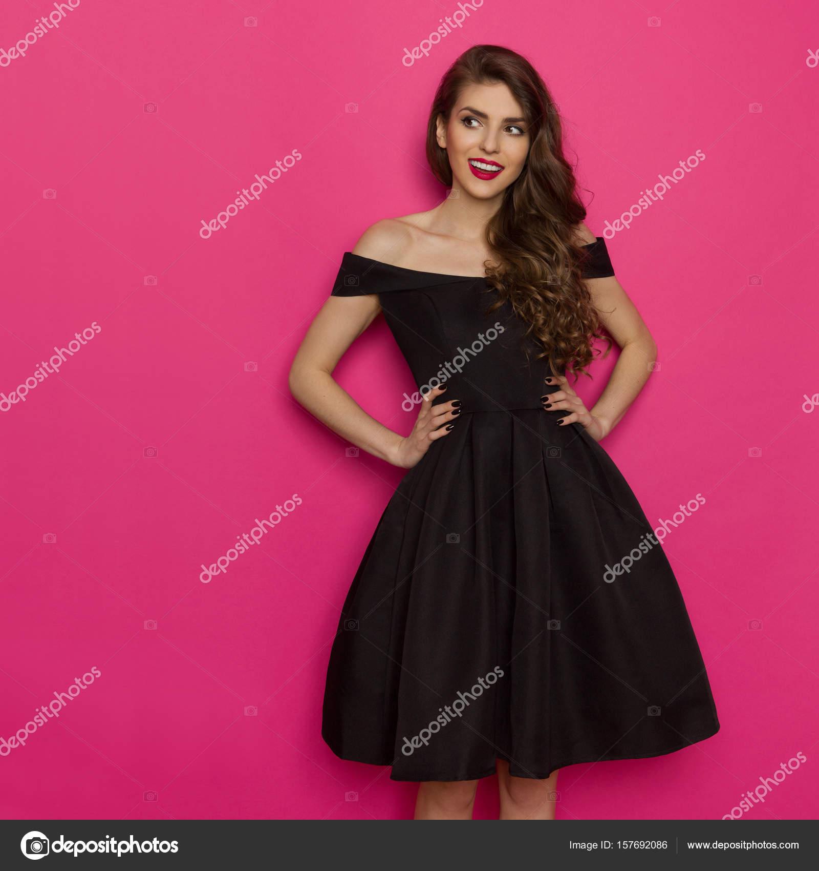 e55956fe5cc Belle jeune femme en robe de cocktail noire élégante est main dans la main  sur la hanche et à la recherche de suite. Trois quarts studio longueur  tourné sur ...