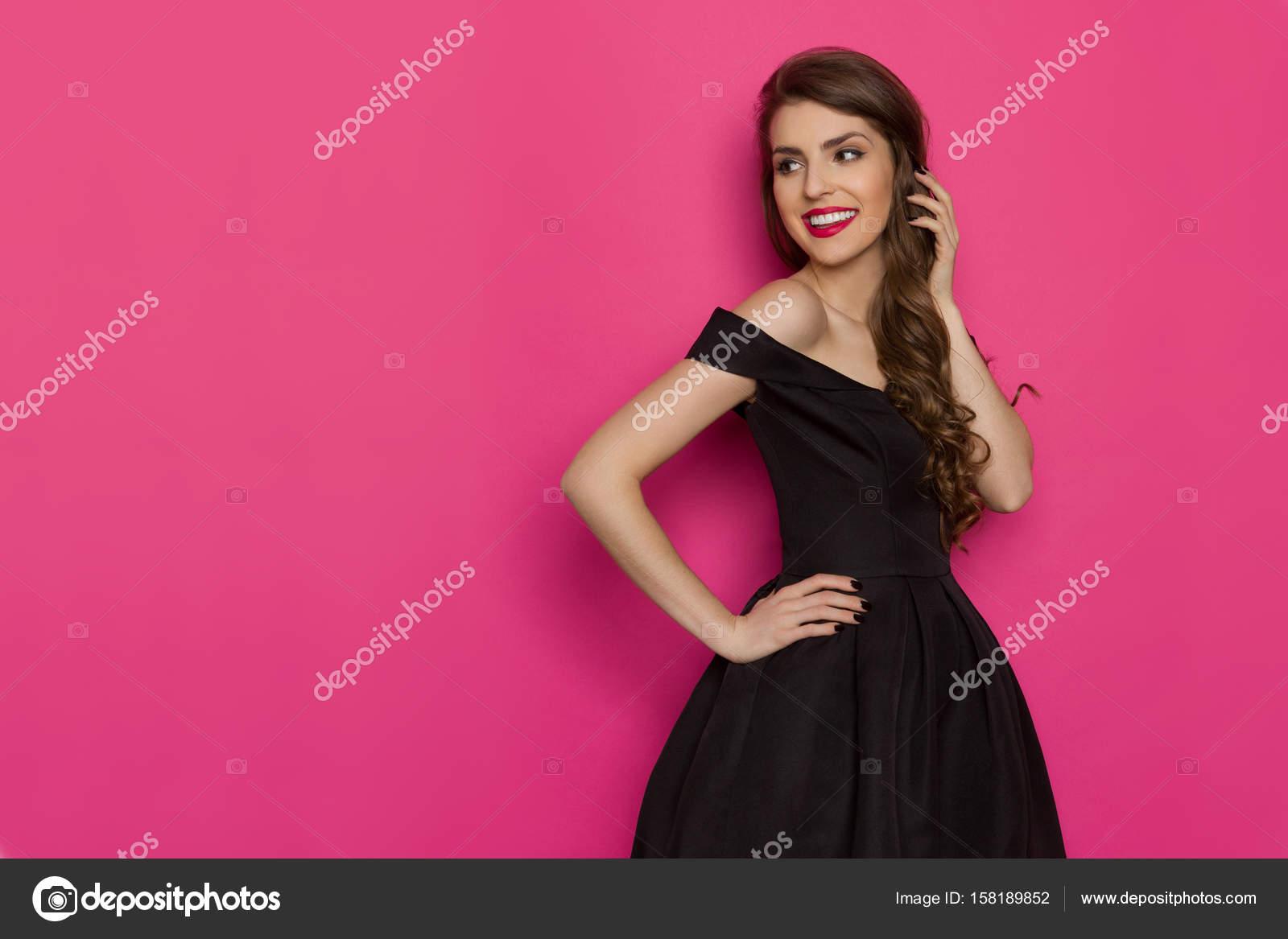 Sonriente mujer elegante vestido negro está mirando lejos — Fotos de ...