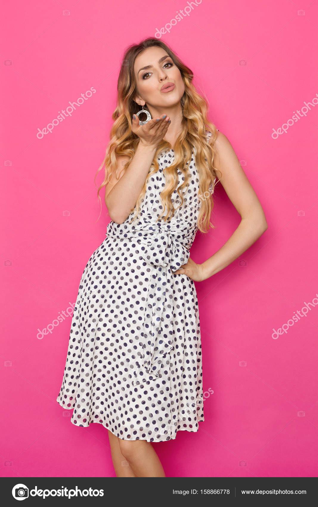 56b7b7ff4466 Vacker kvinna i vit prickig klänning blåser en puss — Stockfotografi ...