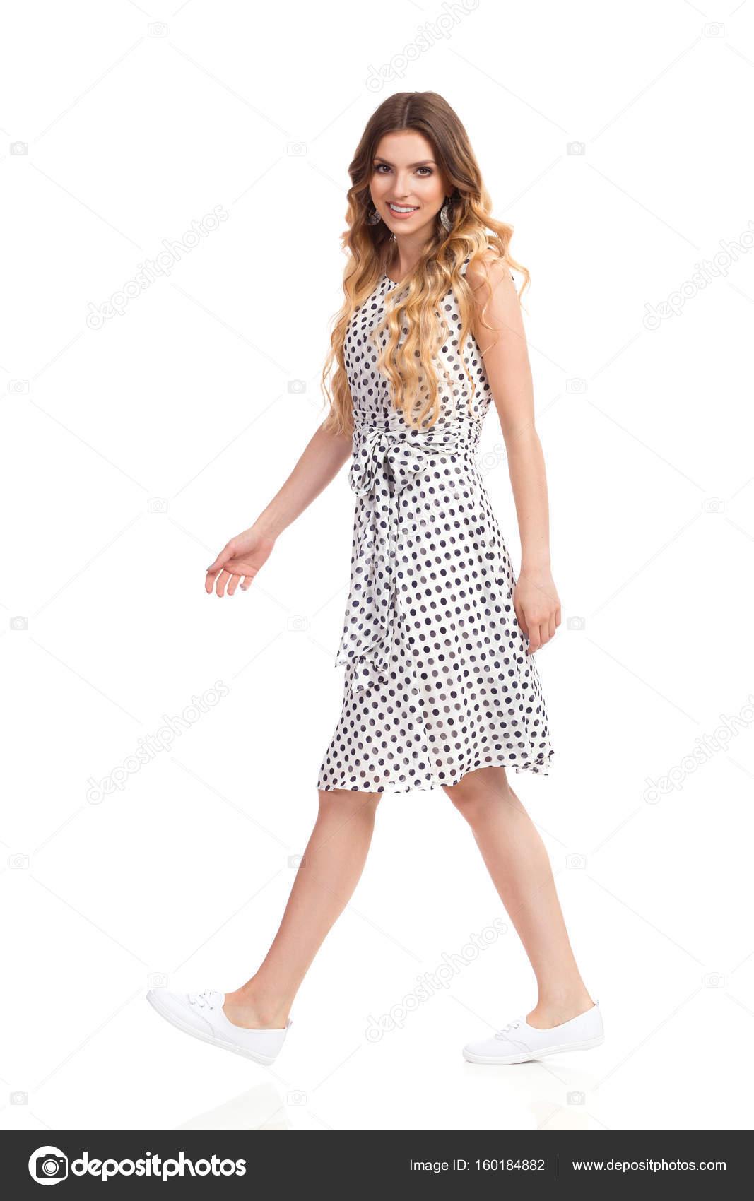 Mujer en vestido de verano blanco es caminando y mirando a cámara — Foto de  Stock ae8c6411a019