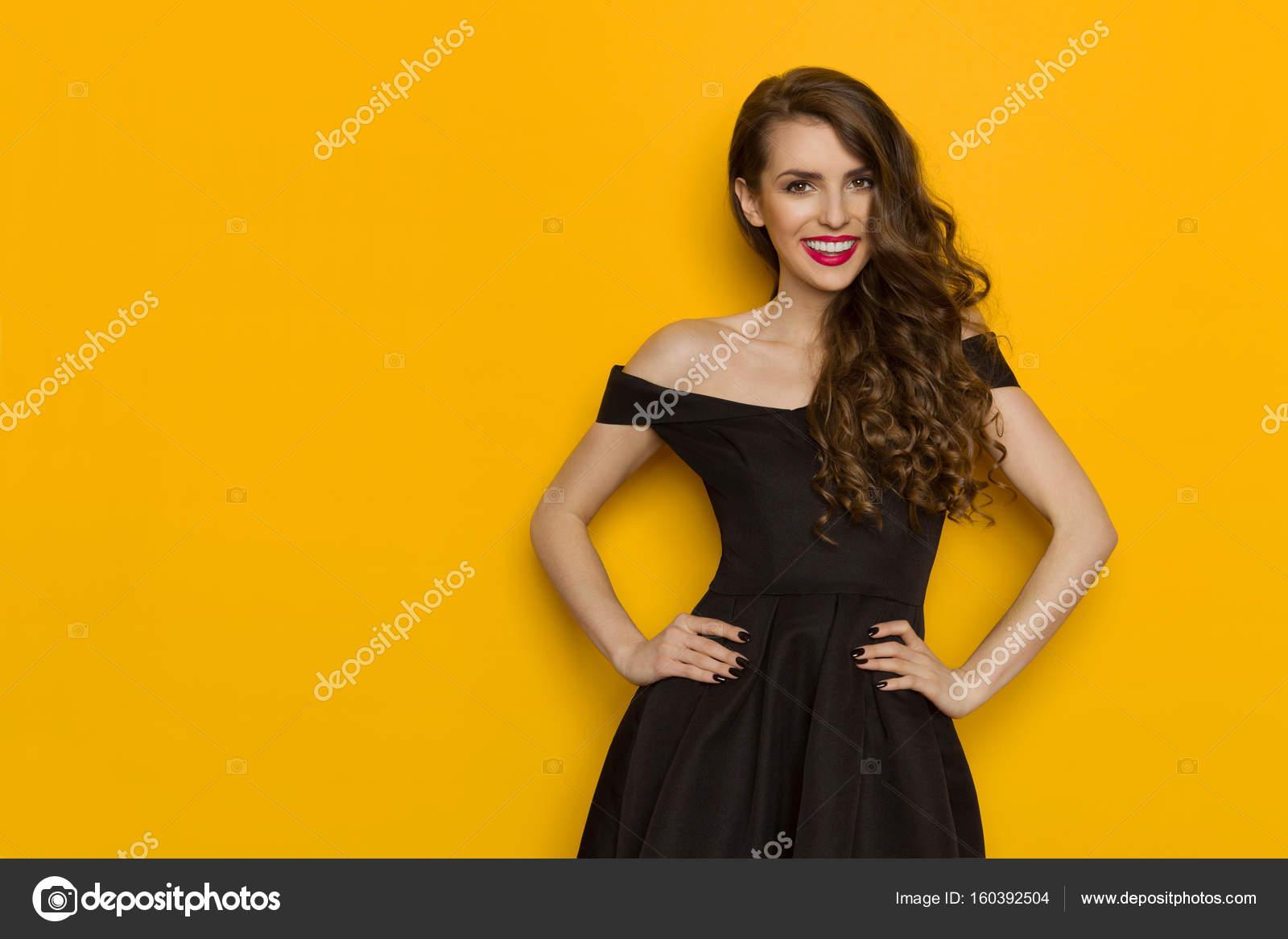 b582107ed5c Belle jeune femme en robe de cocktail noire élégante est main dans la main  sur la hanche