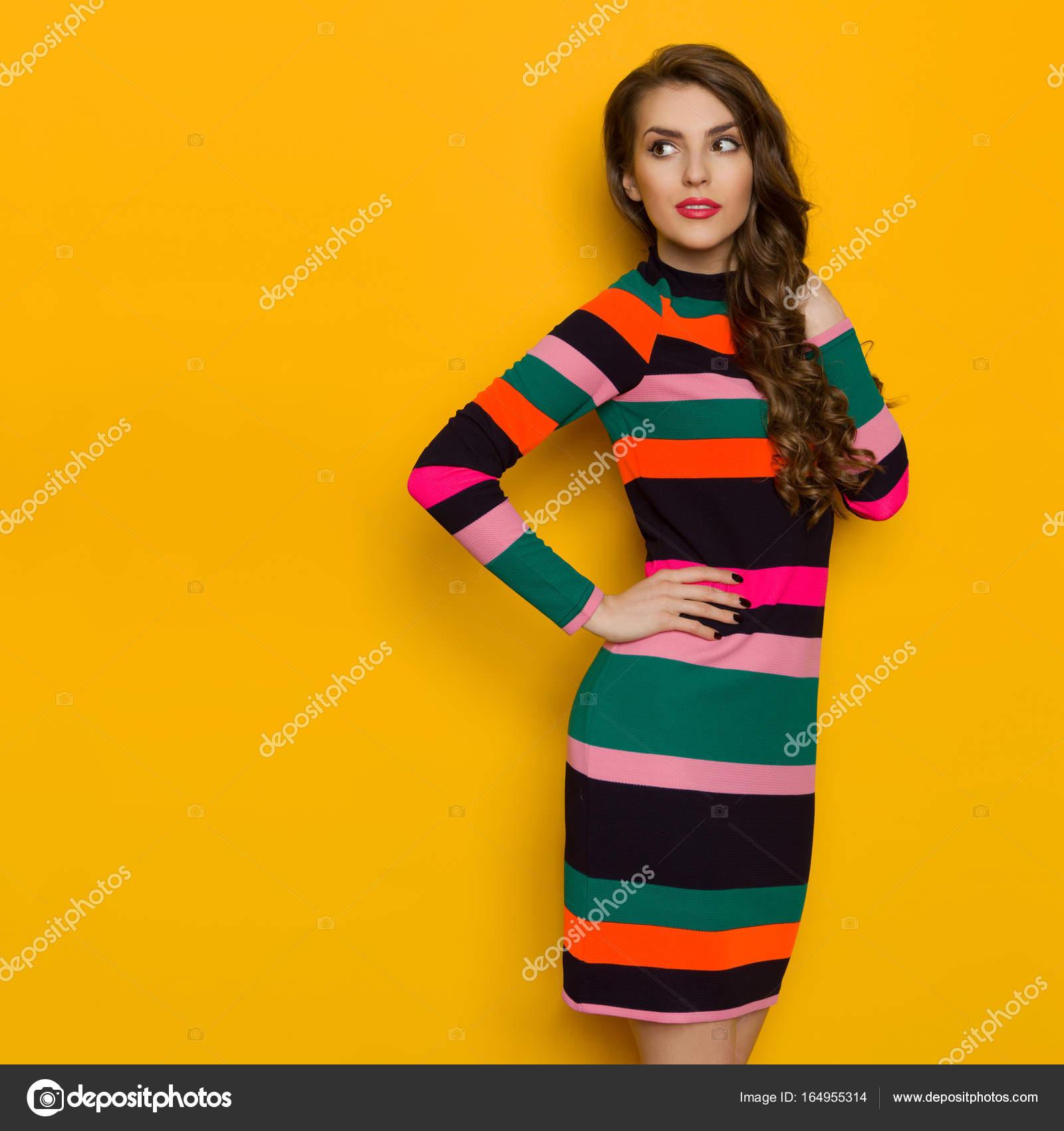 Schöne Frau In lebendige gestreiften Kleid sucht Weg über die ...