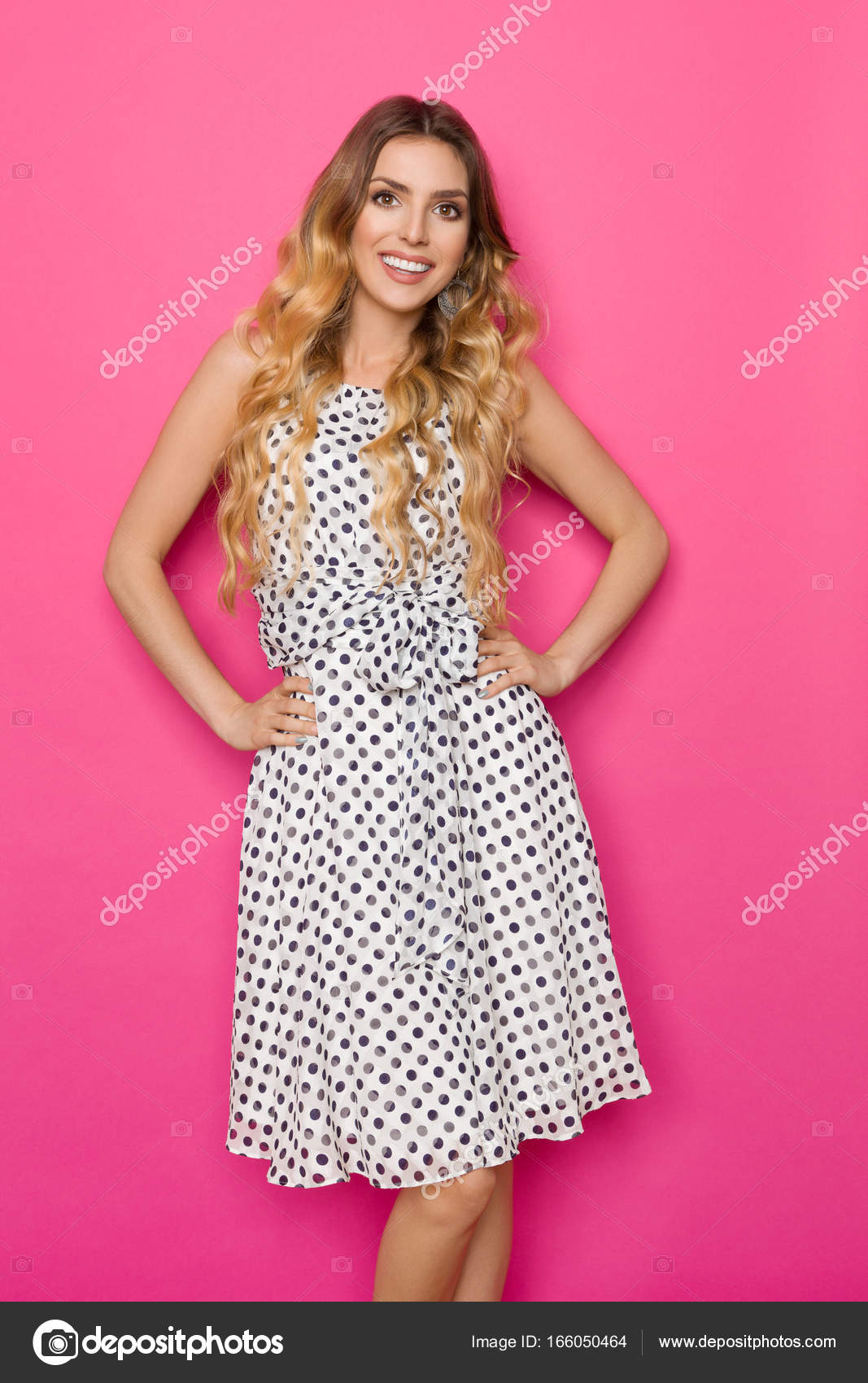 e5bae0c85a97 Beautiful young woman in white dotted summer dress is holding hands on hip