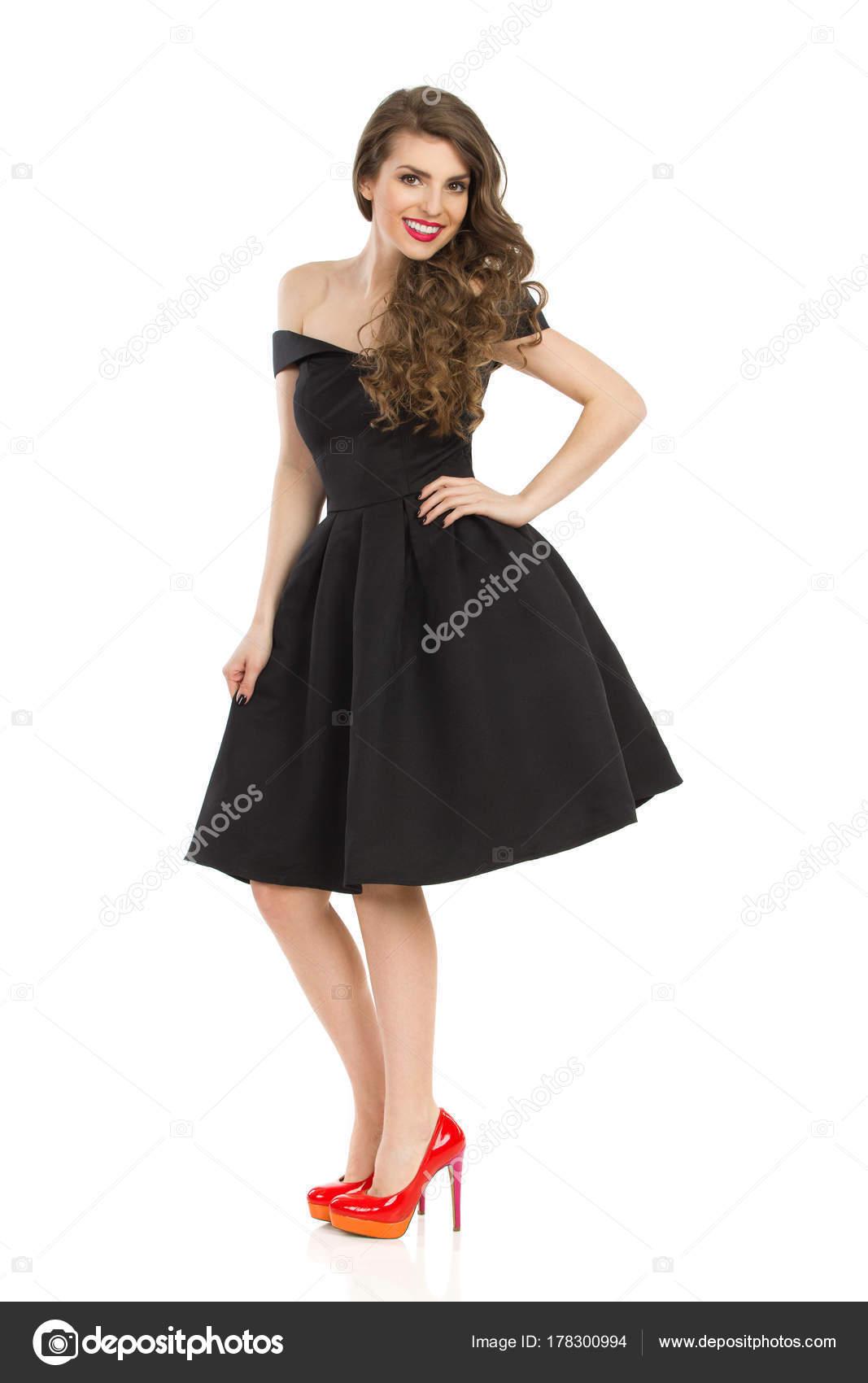 Elegante junge Frau im schwarzen Cocktailkleid und roten High Heels ...