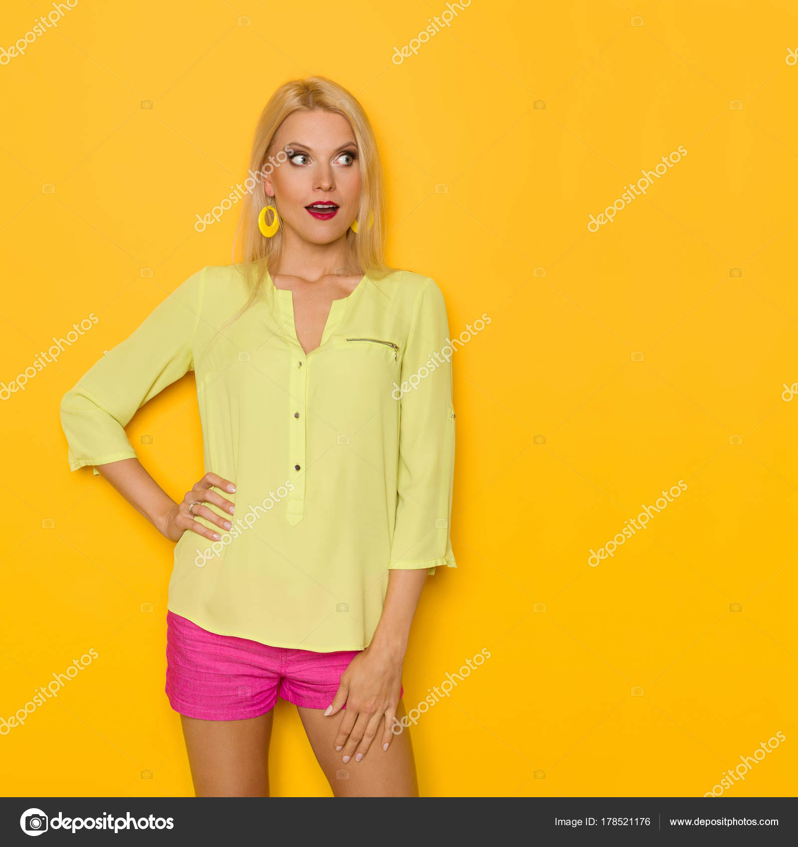 40277533e2b45 Surprised Beautiful Blond Woman In Yellow Shirt And Pink Shorts Is Looking  Away — Stock Photo
