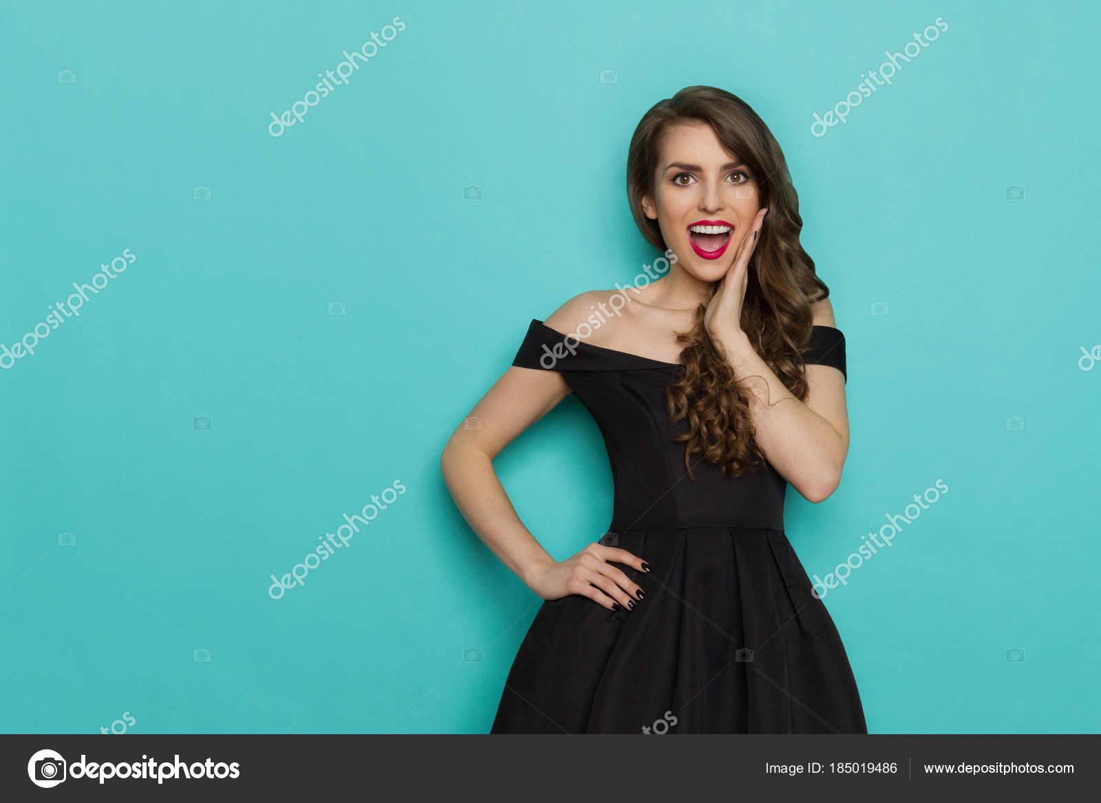 Elegante Dame im schwarzen Cocktailkleid hält Hand am Kinn und ...