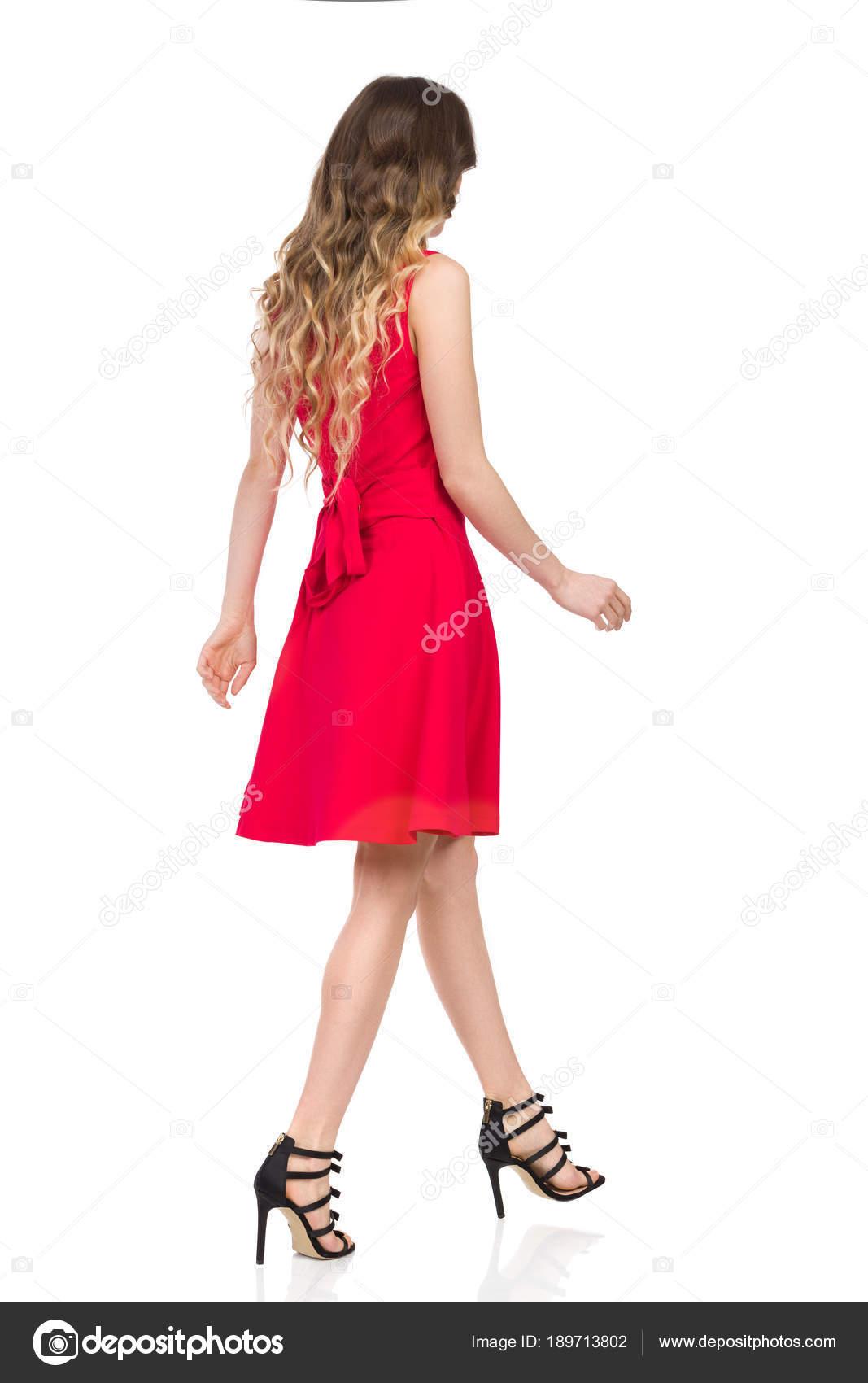 279983a9152 Belle jeune femme en talons hauts noirs et rouge mini robe est à pied. Vue  latérale arrière. Studio de pleine longueur coup isolé sur blanc — Image de  ...