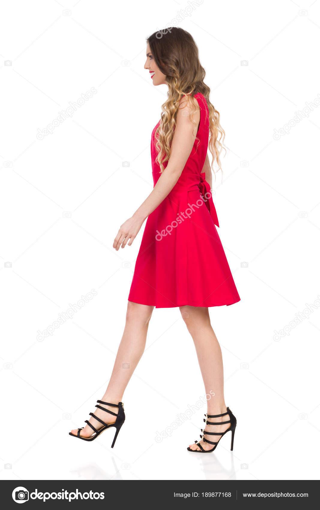 44287790825 Belle jeune femme en talons hauts noirs et rouge robe mini marche