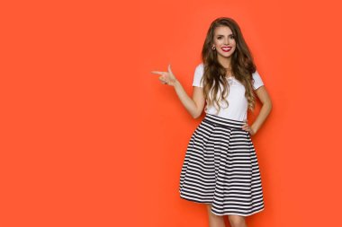 Happy Beautiful Young Woman In Striped Skirt Is Pointing