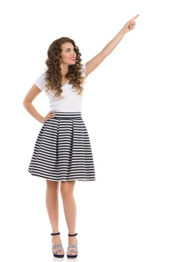 Woman In Striped Skirt And High Heels Is Pointing Up And Looking Away