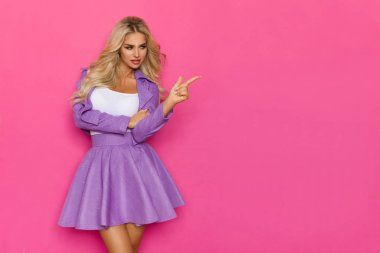 Sexy Blond Woman In Violet Costume Is Pointing At The Side