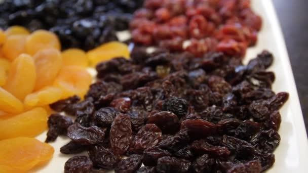 egy tál szárított gyümölcs. mazsola, szárított sárgabarack, szilva, szárított cseresznye. Közelkép. Makró. A kamera körbe-körbe mozog jobbra.
