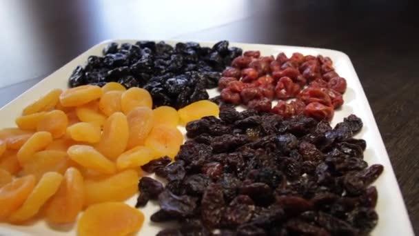 egy tál szárított gyümölcs. mazsola, szárított sárgabarack, szilva, szárított cseresznye. A kamera körbe-körbe mozog jobbra.