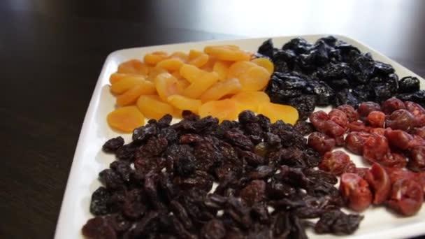 egy tál szárított gyümölcs. mazsola, szárított sárgabarack, szilva, szárított cseresznye. A kamera körbe-körbe mozog itt balra.