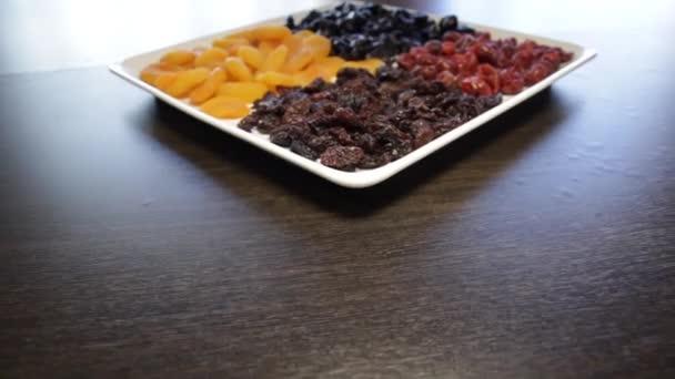 egy tál szárított gyümölcs. mazsola, szárított sárgabarack, szilva, szárított cseresznye. A kamera átrepül ezen előre.
