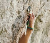 Female climber inserts a quickdraw in anchor on rock wall, outdoor