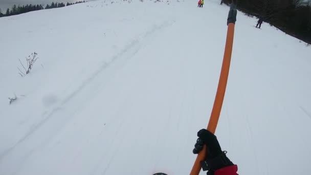 Snowboarder am Schlepplift, Lift zieht Skifahrer an die Spitze der Piste.
