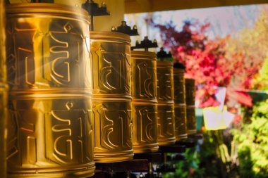 Bhuddhist prayer wheel golden inscribed with a sanskrit prayer and creamy bokeh .