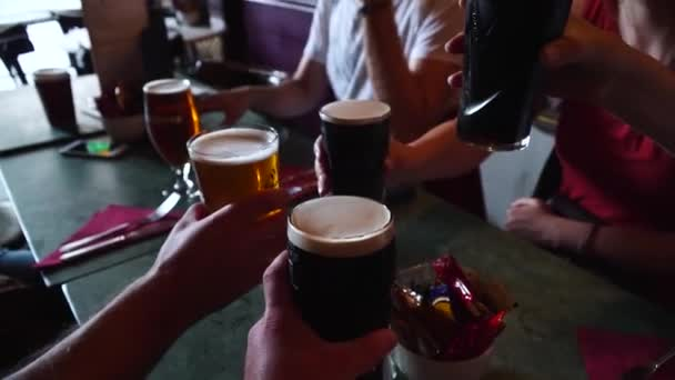 Edinburgh, Scotland - 07 20 2018: Friends at a table in a cafe or bar clink glasses and drink beer