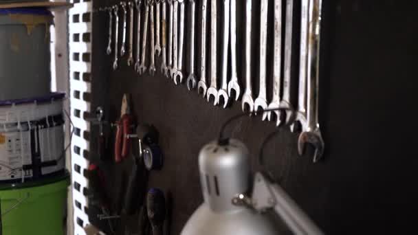 A közeli férfi munkás nyitott végű kézikulcsokat lógat a műhelyében egy fekete deszkán. Garázs előkészítése kézi szerszámokkal végzett munkához.