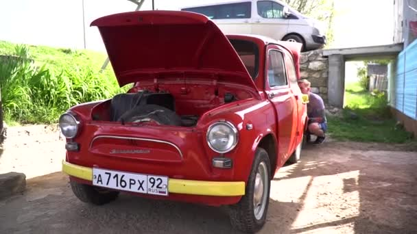 Gelendzhik, Russia - 05 01 2019: Old vintage retro red car ZAZ stay on street with open trunk and hood. People would buy this car