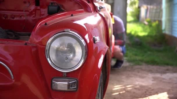 Detailní záběr reflektoru starého červeného klasického auta. Světlomet má chrom s leštěným rámečkem. Signál zhasněte pod světlometem historického automobilu.
