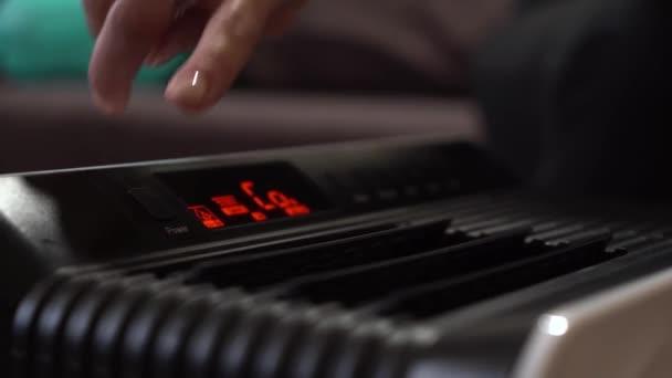 Holka zapne zvlhčovač. Okenice zařízení se otevřou a osoba začne přepínat režimy pomocí černých tlačítek na samotném zařízení.